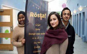 Bild på tre stycken demokratiambassadörer som står vid en skylt med texten Rösta!